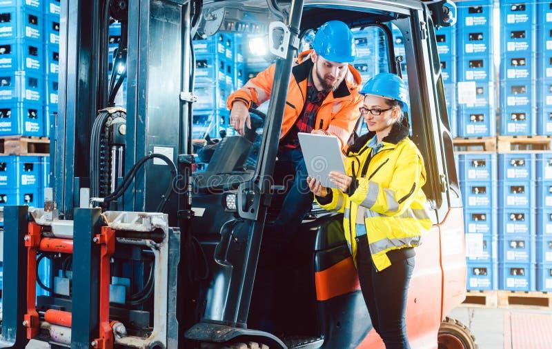 Lavoratori nel magazzino di logistica che controllano l'inventario immagine stock libera da diritti