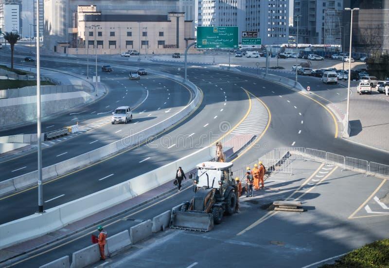 Lavoratori riparazione della strada e pulire le vie nelle prime ore del mattino con un trattore fotografia stock