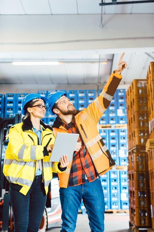 Lavoratori in un magazzino di logistica che progetta il progetto seguente fotografie stock libere da diritti