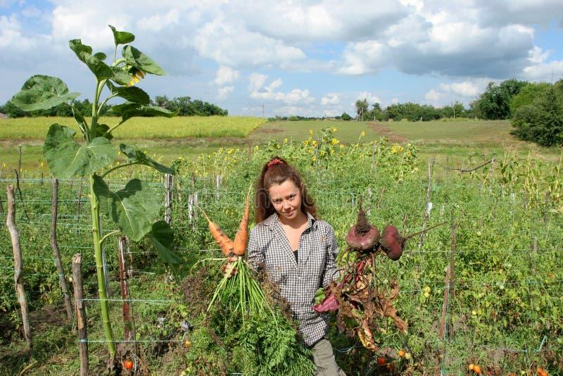 Lavoratrice agricola con il raccolto in sua mano fotografia stock libera da diritti