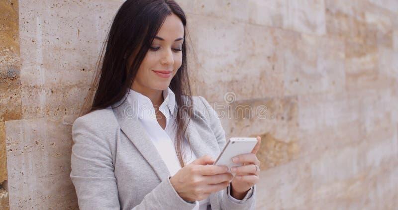 Lavoratrice che manda un sms e che pende contro la parete fotografia stock libera da diritti