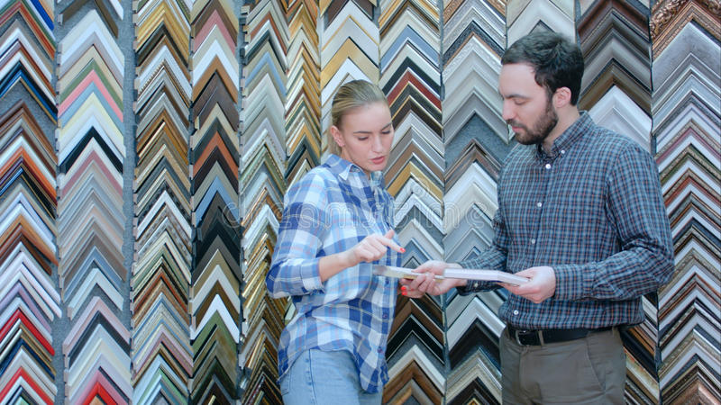 Lavoratrice che parla con il cliente circa i dettagli della cornice in atelier immagine stock libera da diritti