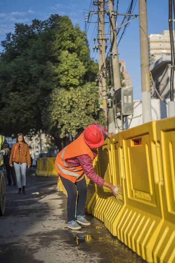 Lavoratrice che porta i camici arancio che portano un casco e che puliscono il cantiere fotografie stock libere da diritti