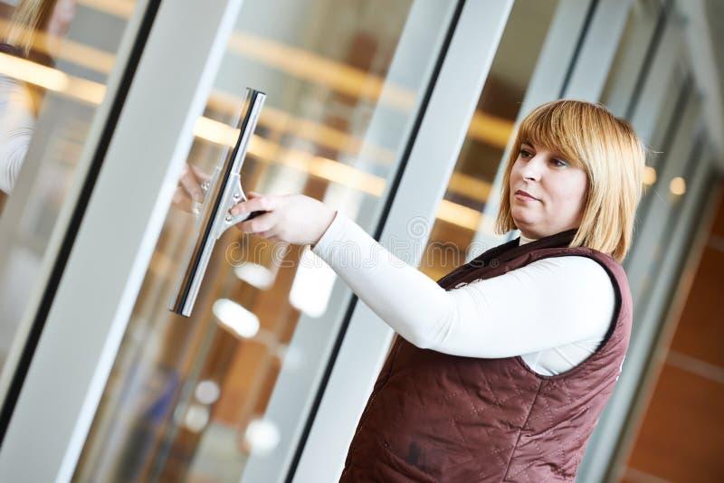 Lavoratrice che pulisce finestra dell'interno immagini stock libere da diritti