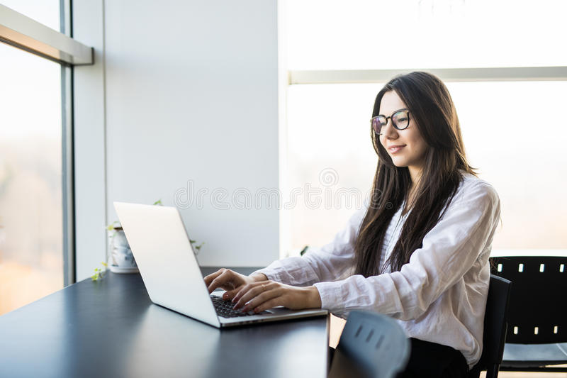 Lavoratrice che si siede nell'ufficio mentre per mezzo del computer portatile e scrivendo dalla tastiera immagine stock