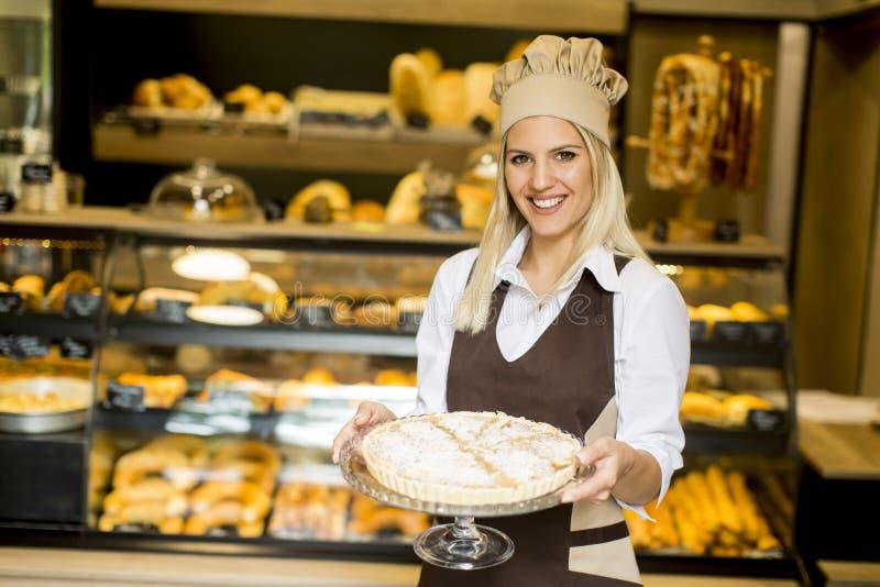 Lavoratrice del forno che posa con la crostata di mele nel negozio del panettiere immagine stock