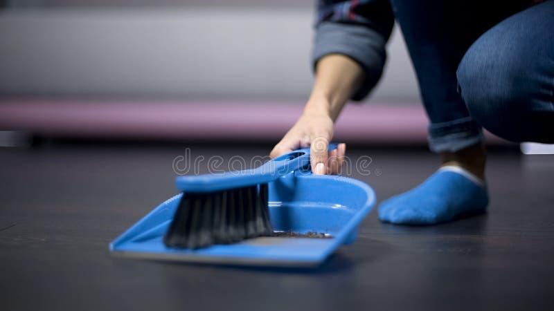 Lavoratrice migratore che spolvera il pavimento con una spazzola, pagata male occupazione immagine stock
