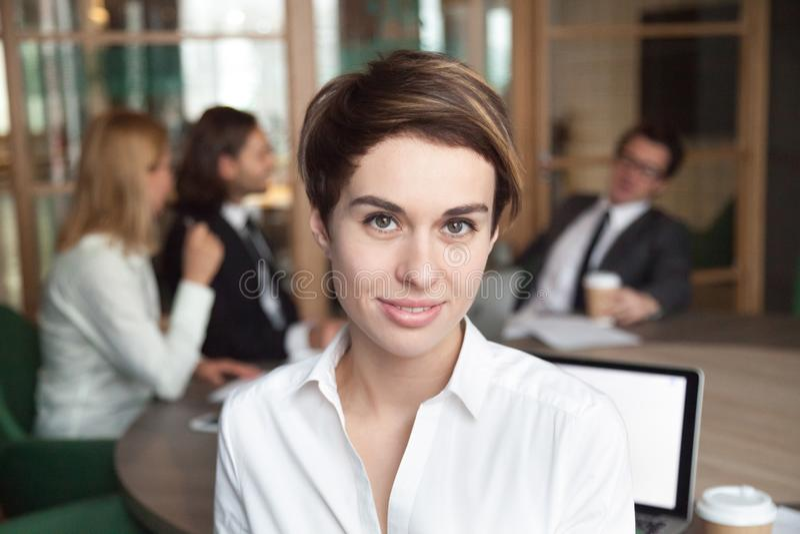 Lavoratrice sorridente che posa per il catalogo di affari della società fotografia stock