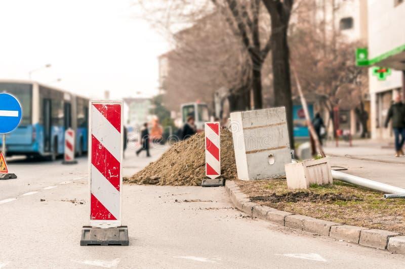 Lavori avanti il sito di ricostruzione della via con il segno e recinti come barriera della strada immagini stock