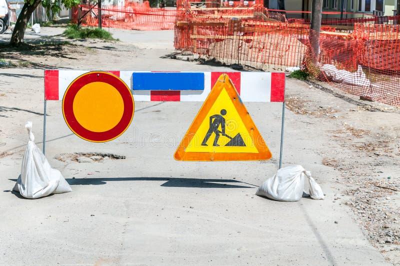 Lavori avanti il sito di ricostruzione della via con il segno e recinti come barriera della strada immagine stock