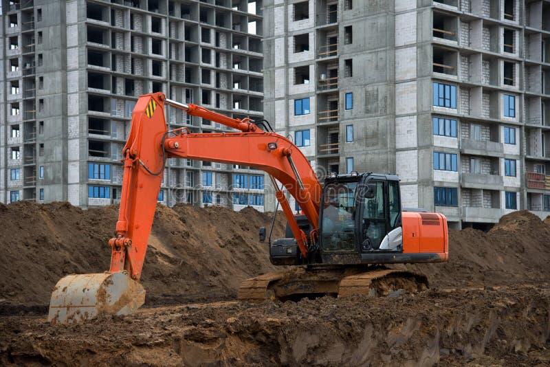 Lavori di scavo in cantiere Il retro scava il terreno per la fondazione e per l'estrazione della linea fognaria immagini stock