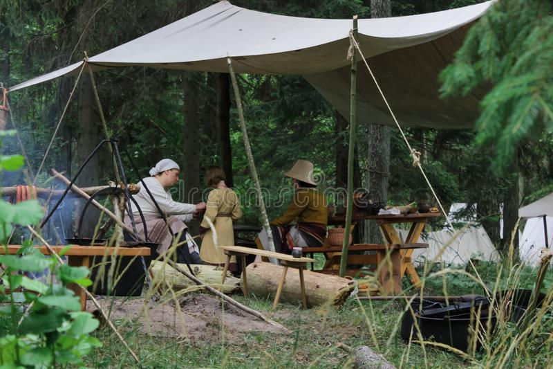 Lavori domestici quotidiani nel campo della tenda dei reenactors dei medio evo giovani fotografia stock
