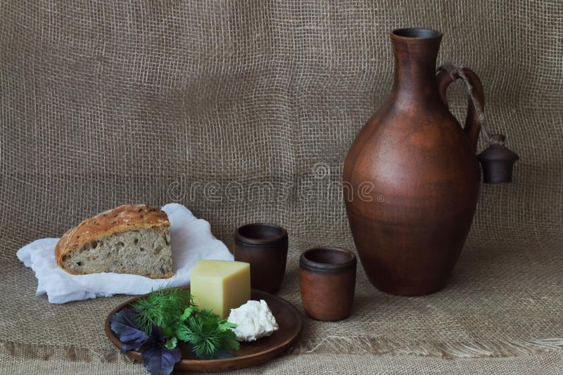 Lavori forzati e formaggio a pasta molle con i verdi sul piatto rotondo dell'argilla, sulla brocca per vino, sulla tazza e sul pa fotografie stock libere da diritti