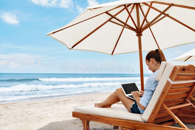 Lavoro alla spiaggia Donna di affari che lavora online sul computer portatile all'aperto fotografia stock libera da diritti