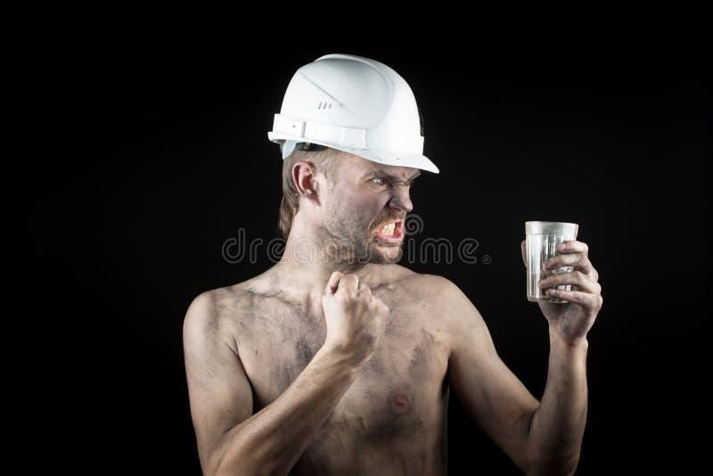 Lavoro arrabbiato in un casco sporco fotografia stock libera da diritti
