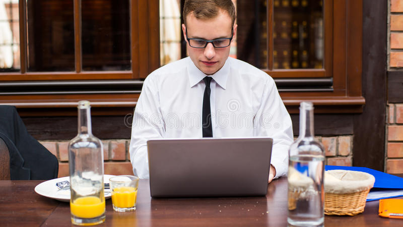 Lavoro bello dell'uomo d'affari al computer portatile in ristorante. immagine stock
