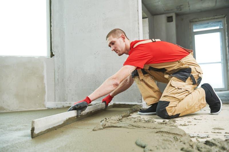 Lavoro del cemento del pavimento Intonacatore che liscia la superficie del pavimento con screeder fotografie stock libere da diritti