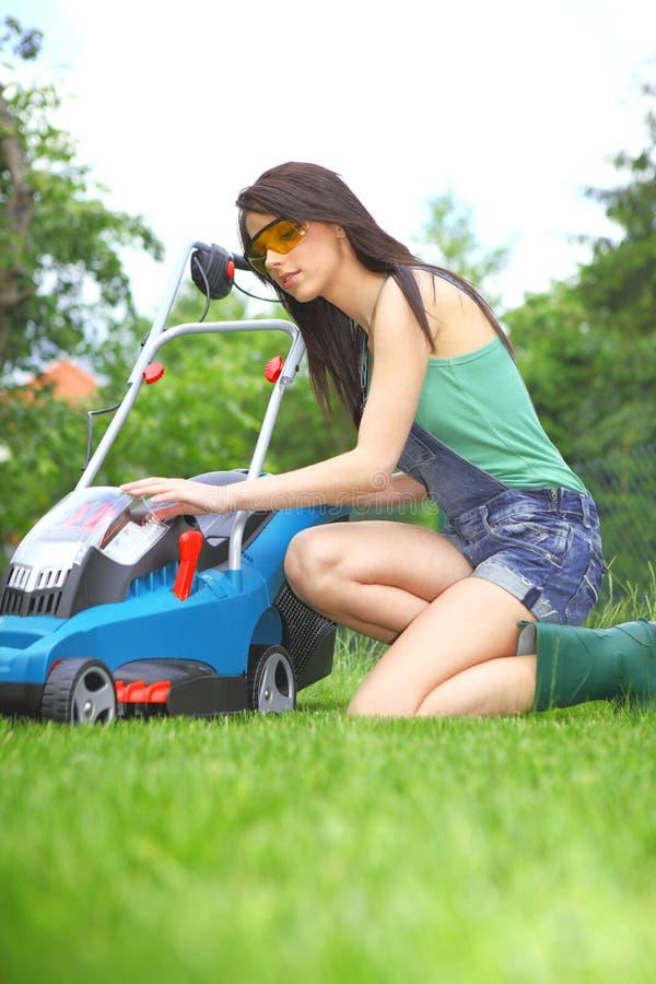 Lavoro del giardino, erba di falciatura della donna con la falciatrice immagine stock