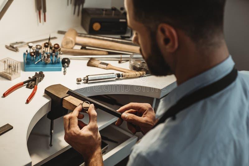 Lavoro delicato dei gioielli Chiuda su di un gioielliere maschio che lavora e che modella un anello non finito con uno strumento  immagini stock