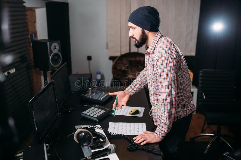 Lavoro dell'ingegnere sano con il disco nello studio di musica immagini stock