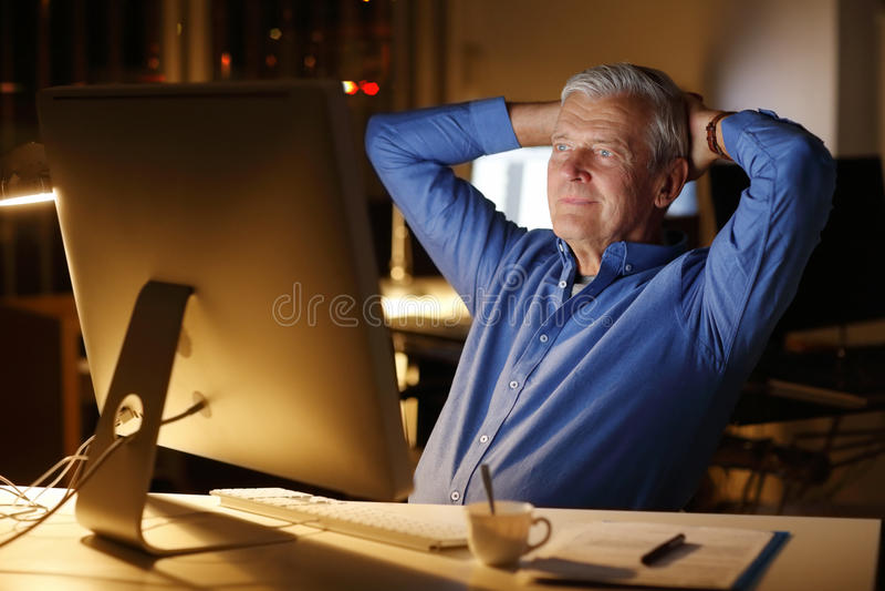 Lavoro dell'uomo senior a tarda notte fotografia stock