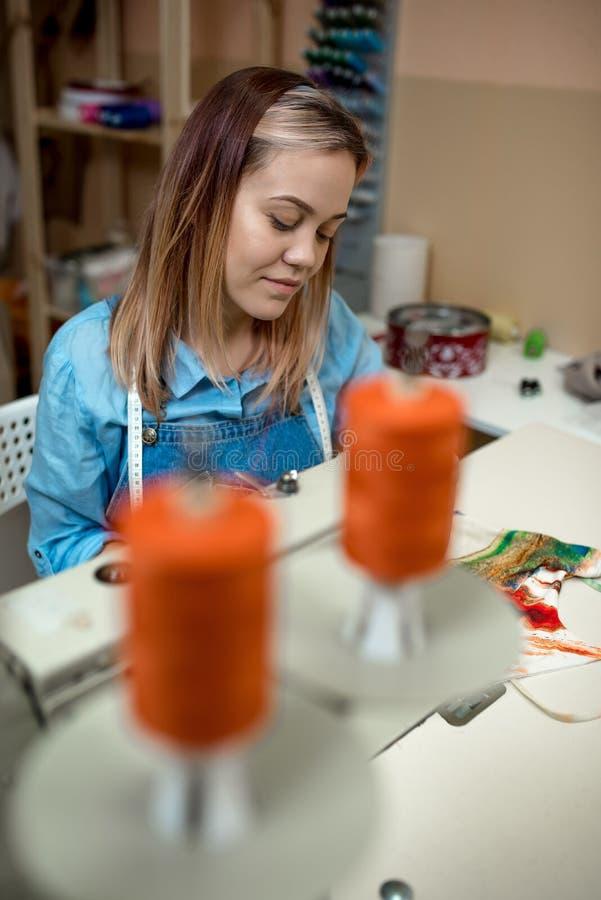 Lavoro della cucitrice della donna nell'officina sulle macchine per cucire fotografia stock
