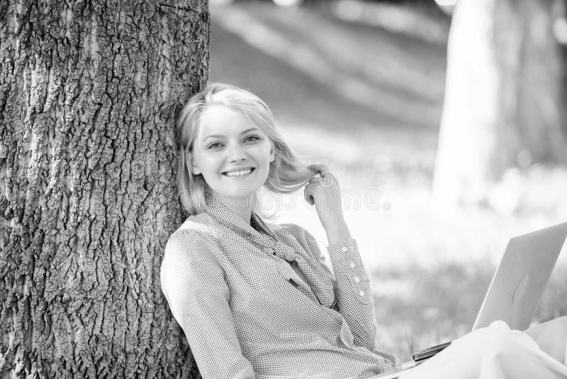 Lavoro della ragazza con il computer portatile in parco sedersi su erba Tecnologia di istruzione e concetto di Internet Ufficio d fotografie stock libere da diritti