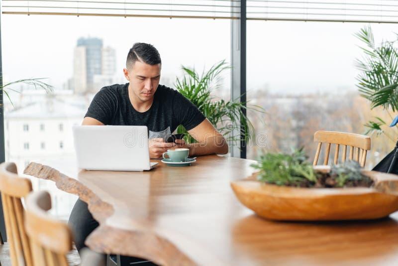 Lavoro delle free lance su netbook nel coworking moderno Caff? bevente del giovane da una tazza Programmatore al lavoro a distanz fotografia stock libera da diritti
