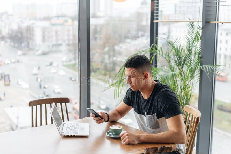 Lavoro delle free lance su netbook nel coworking moderno Caff? bevente del giovane da una tazza Programmatore al lavoro a distanz fotografia stock
