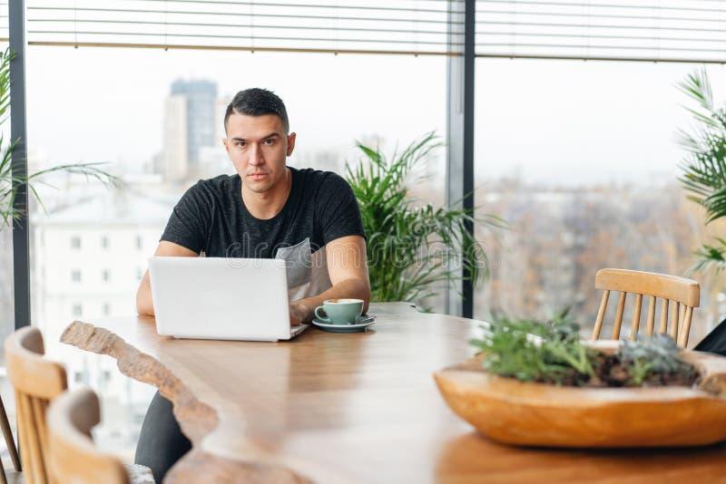 Lavoro delle free lance su netbook nel coworking moderno Caff? bevente del giovane da una tazza Programmatore al lavoro a distanz fotografie stock