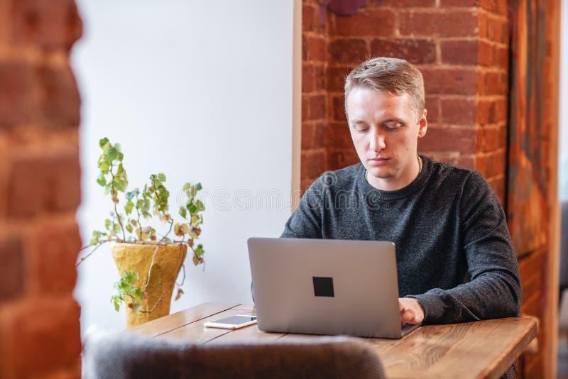 Lavoro delle free lance su netbook nel coworking moderno Giovane che scrive su uno smartphone, Programmatore al lavoro a distanza fotografia stock