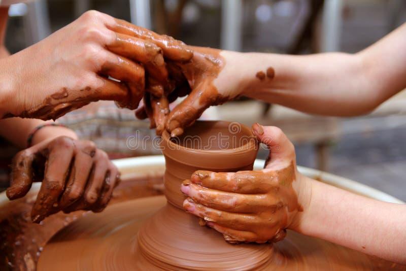 Lavoro delle terraglie della rotella di mani del vasaio dell'argilla fotografia stock libera da diritti