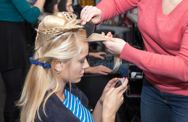 Lavoro dello stilista sui capelli della donna in salone fotografie stock