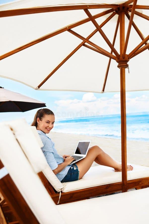 Lavoro di estate Donna che si rilassa facendo uso del computer sulla spiaggia Affare indipendente immagini stock libere da diritti