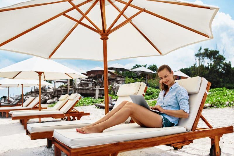 Lavoro di estate Donna che si rilassa facendo uso del computer sulla spiaggia Affare indipendente fotografia stock libera da diritti