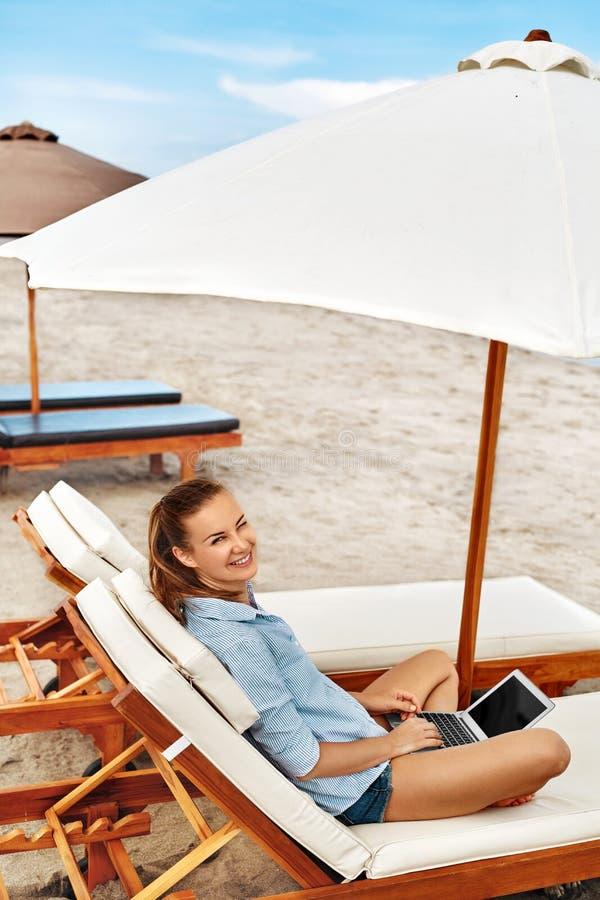 Lavoro di estate Donna che si rilassa facendo uso del computer sulla spiaggia freelance immagine stock