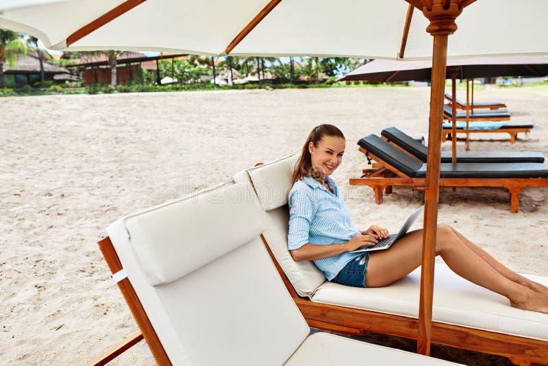 Lavoro di estate Donna che si rilassa facendo uso del computer sulla spiaggia freelance fotografia stock