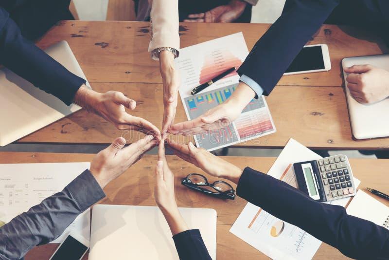 Lavoro di gruppo dei partner che si prende per mano insieme al successo Pila del gruppo di affari di mani per la stella sul proge fotografia stock libera da diritti