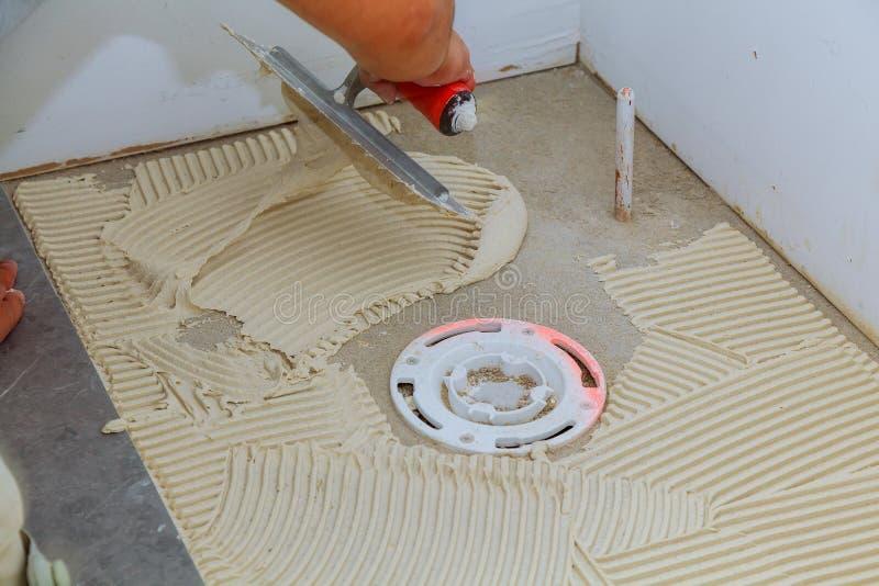 Lavoro di riparazione del gesso e del piastrellista che pone mattonelle, cazzuola in una mano dell'uomo fotografie stock