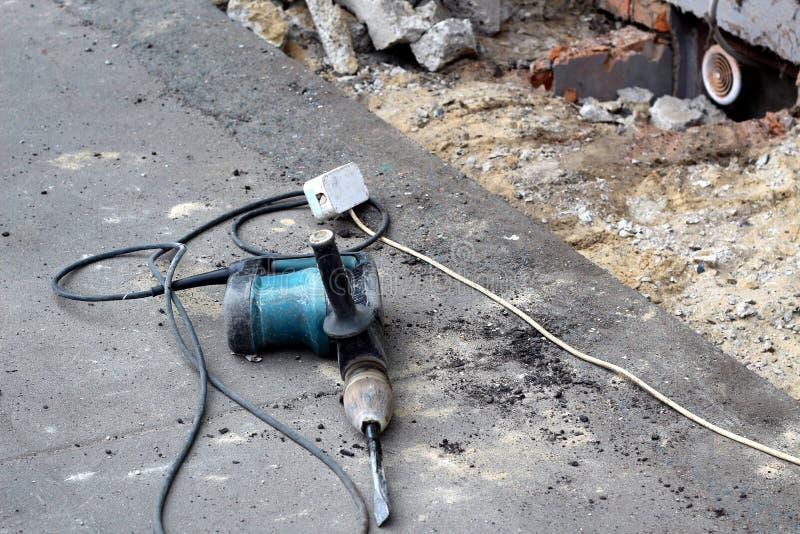 Lavoro di riparazione del marciapiede il martello pneumatico si trova sulla pavimentazione fotografie stock libere da diritti