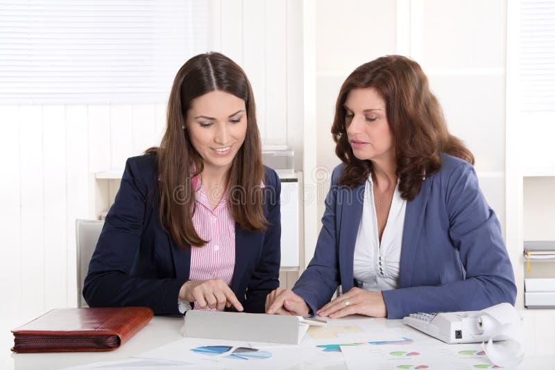 Lavoro di squadra: donna di affari due che lavora insieme. immagine stock