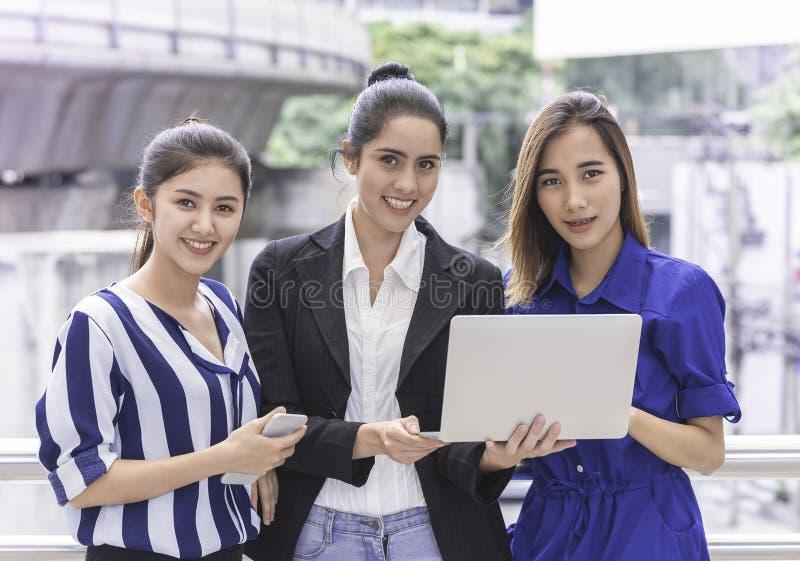 Lavoro di squadra felice dell'amico della donna di affari degli impiegati di concetto sul computer portatile immagini stock