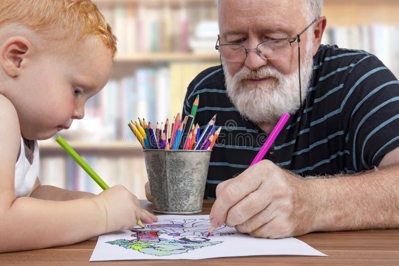 Lavoro di squadra fra il nonno ed il nipote per colorare un disegno fotografie stock libere da diritti