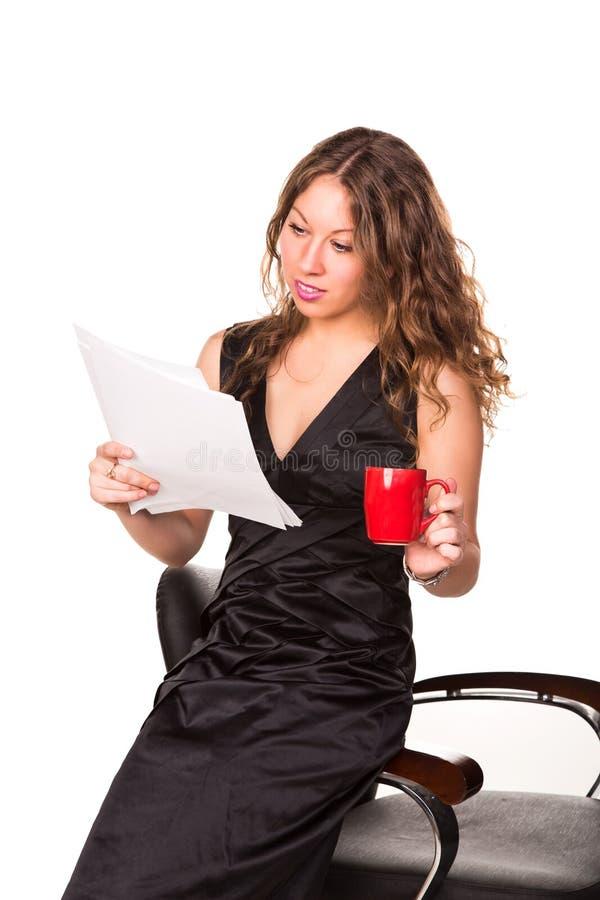 Lavoro di ufficio attraente della lettura della donna di affari mentre godendo di una tazza di caffè fotografia stock