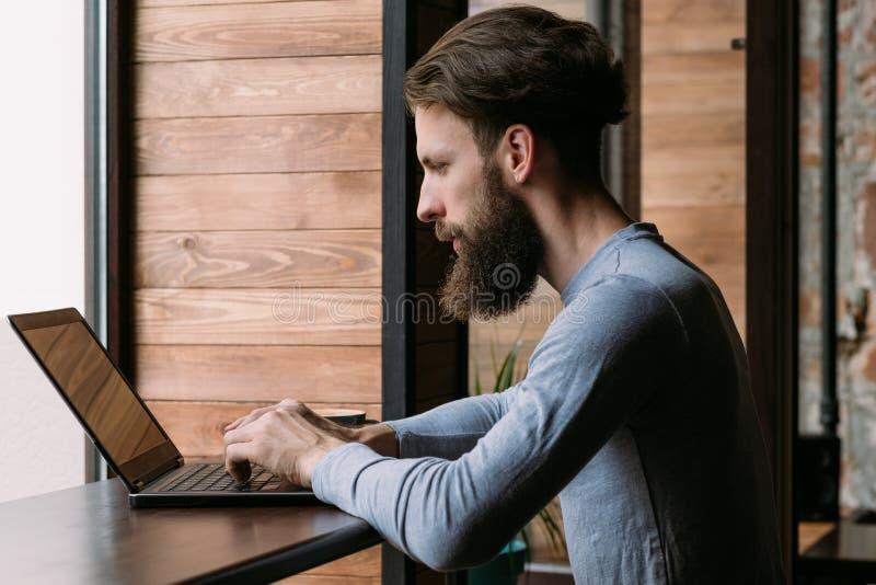 Lavoro a distanza indipendente di lavoro del caffè del computer portatile dell'uomo fotografia stock