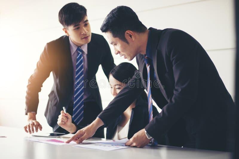 Lavoro e punto degli uomini d'affari sui documenti finanziari del diagramma e di analisi del grafico sulla tavola dell'ufficio fotografie stock