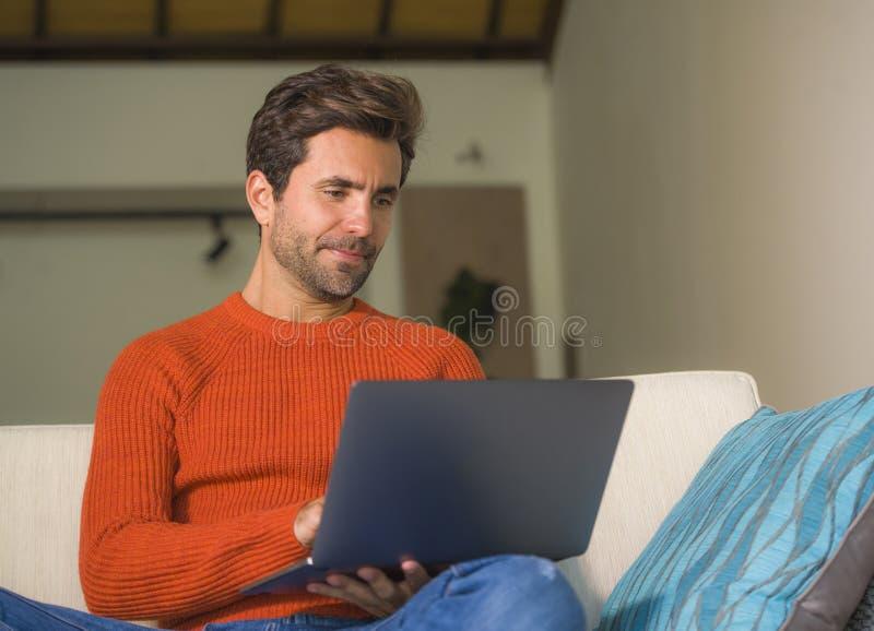 Lavoro felice ed attraente giovane dell'uomo rilassato con il computer portatile al salone moderno dell'appartamento che si siede fotografia stock