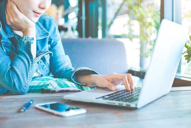 Lavoro manuali della donna in un computer portatile nell'ufficio fotografia stock libera da diritti