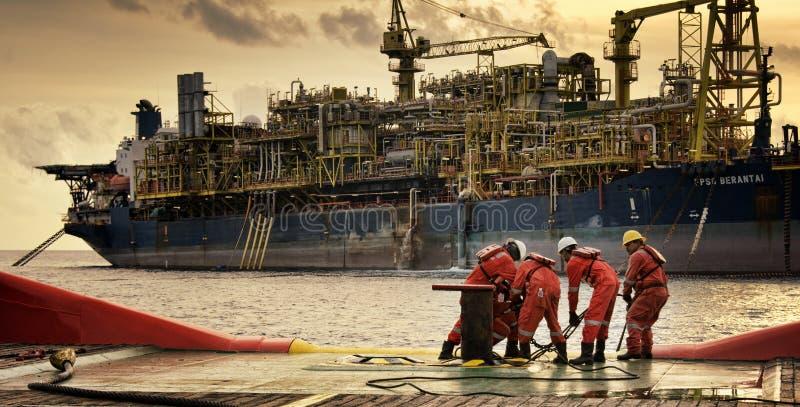 Lavoro marino della squadra alla piattaforma poppiera durante la sera fotografia stock