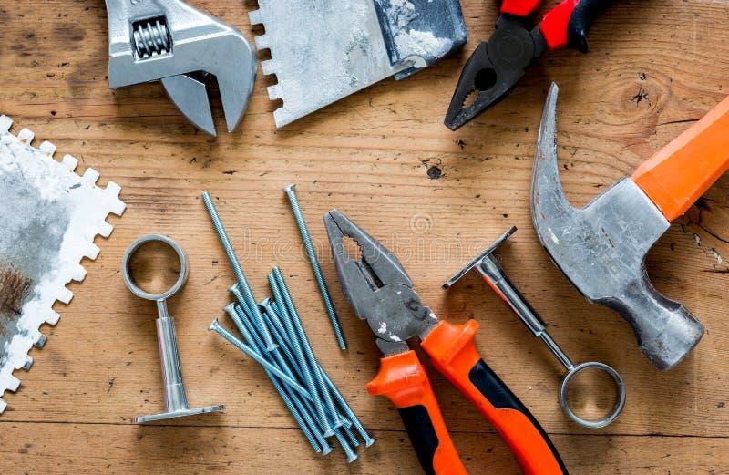 Lavoro professionale del costruttore con gli strumenti di rinnovamento della casa sulla vista superiore del fondo di legno fotografia stock